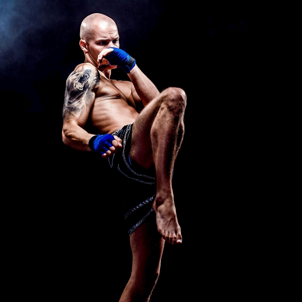 muscular-muay-thai-fighter-punching-darkness-squared