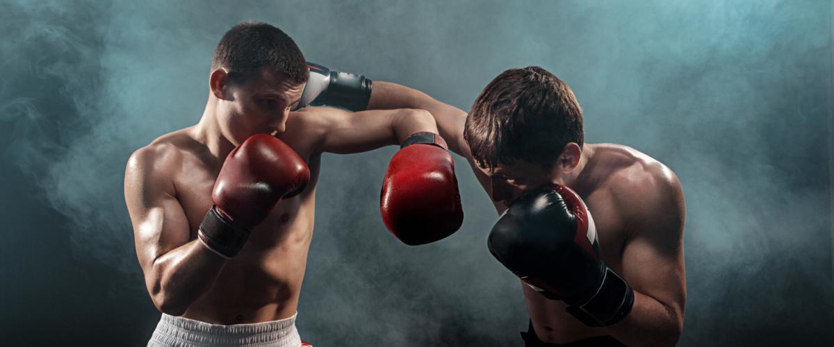 Two professional boxer boxing on black smoky studio background.